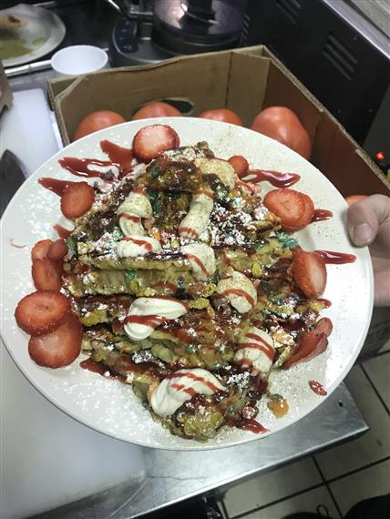 French Toast made with Fruity Pebbles topped with powdered sugar and strawberries being held in a white plate