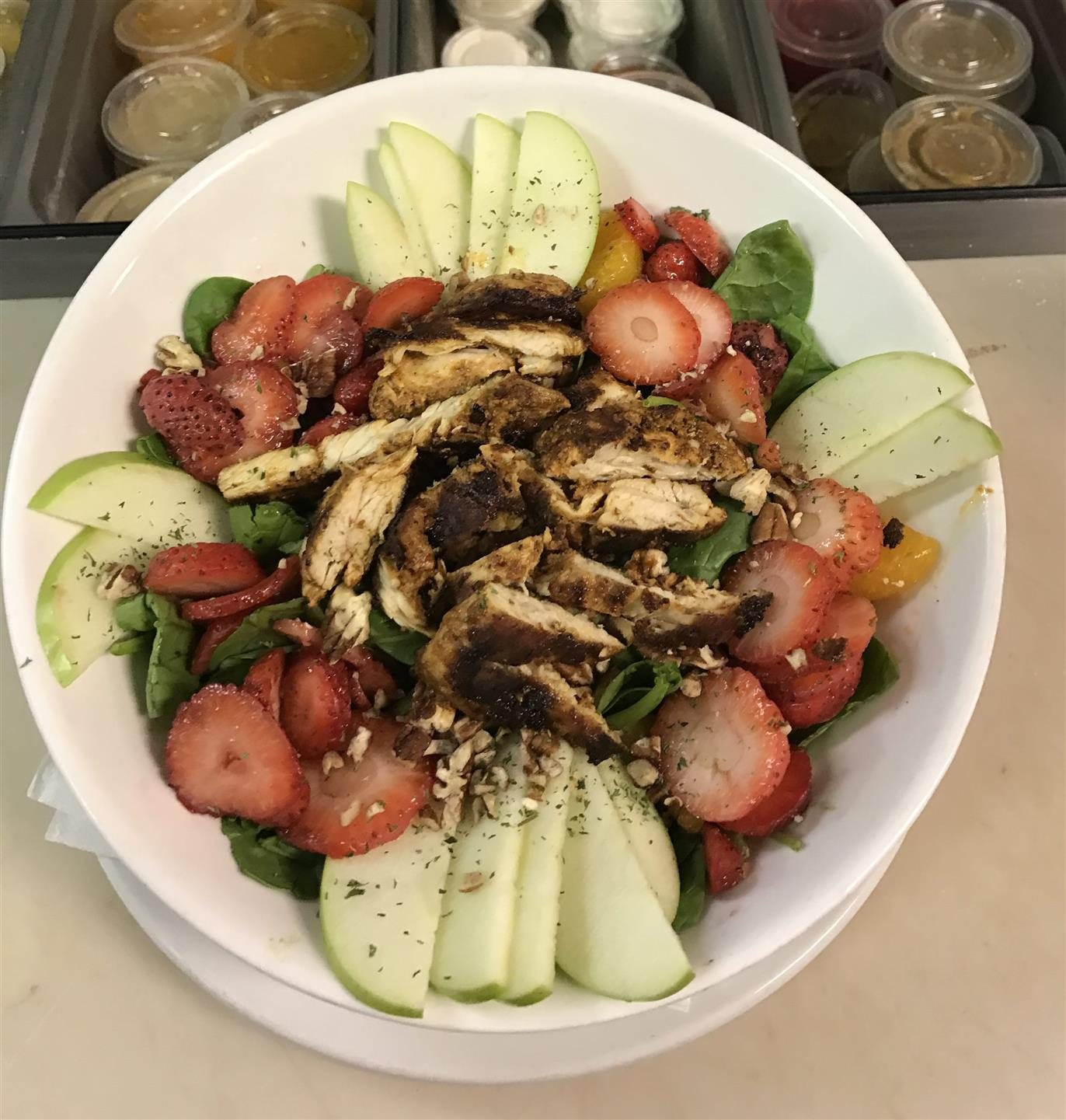 Strawberry Chicken Salad with fresh spinach covered in strawberries, mandarin oranges, green apples, pecans and chicken breast in a white bowl
