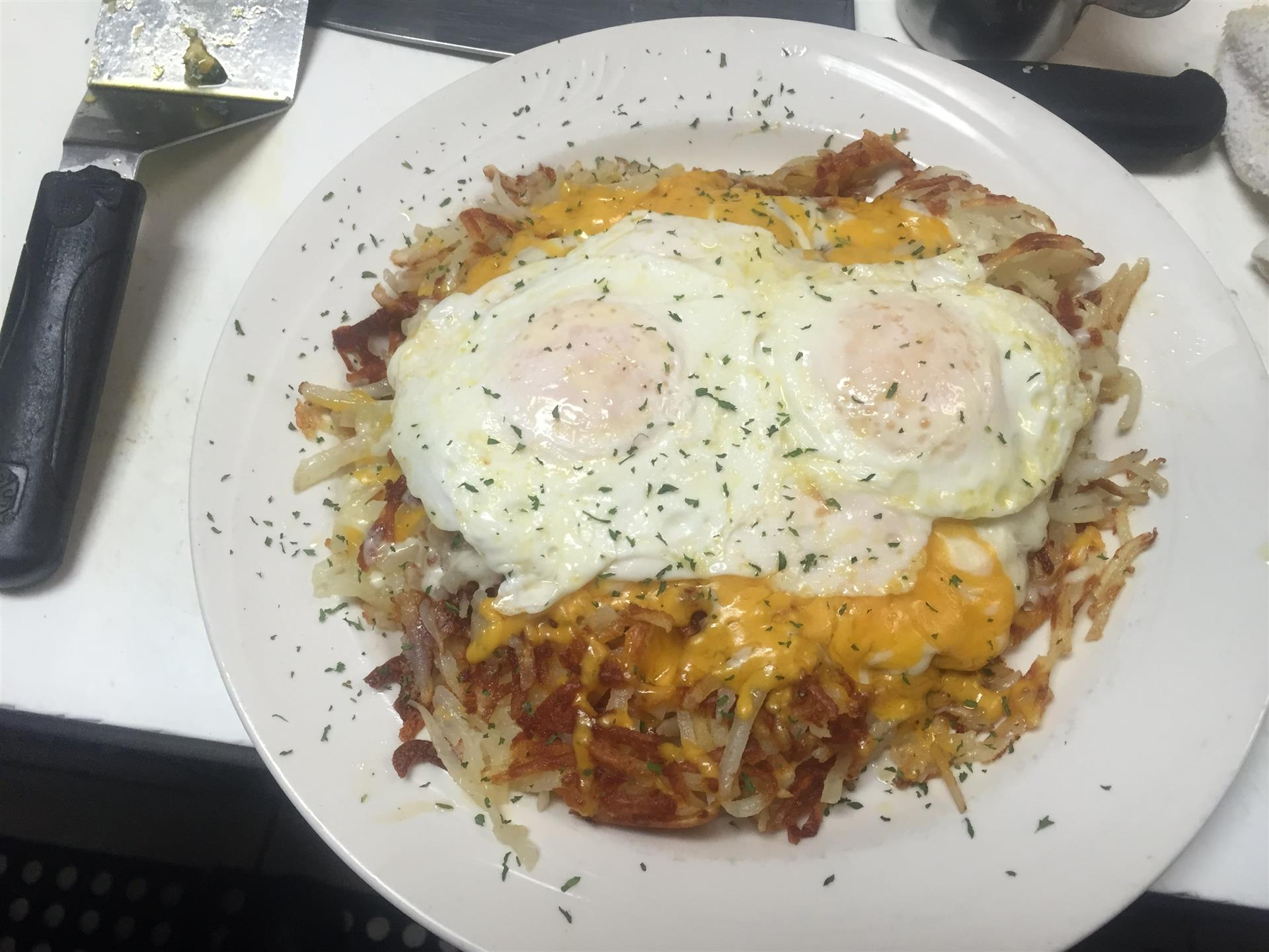 Over Medium Eggs over hashbrowns and cheese on a white plate