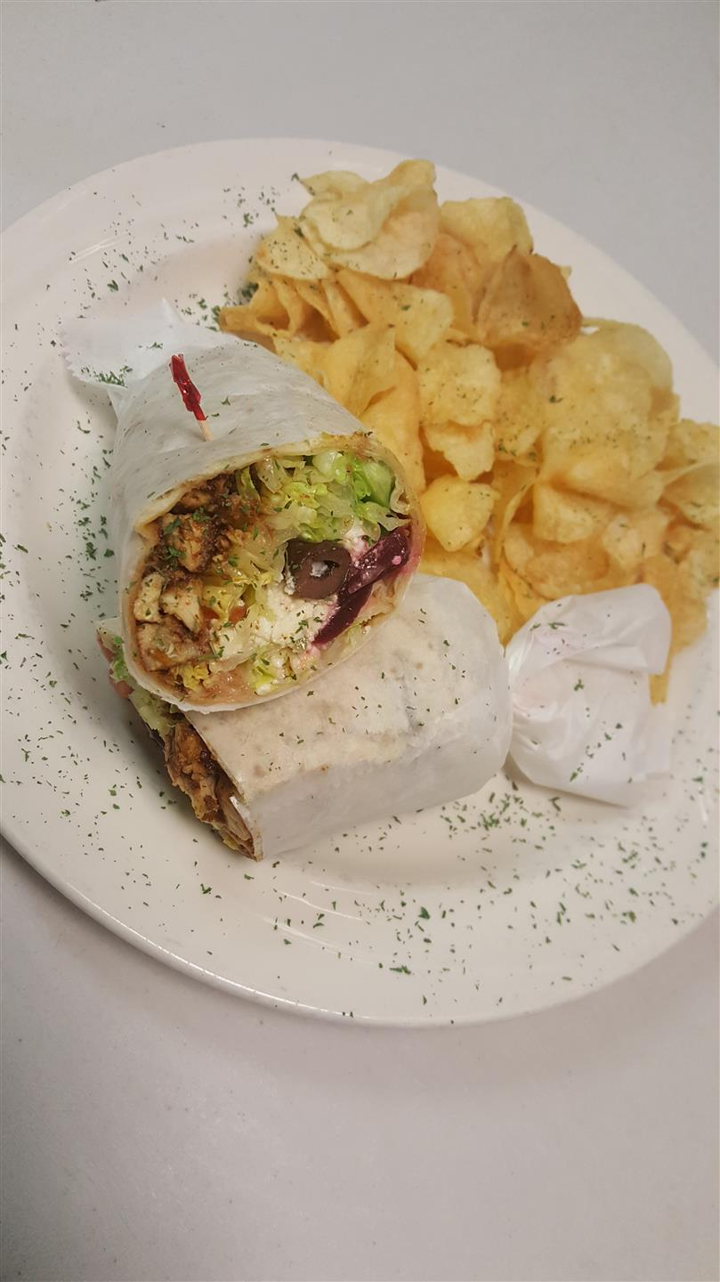 Greek Chicken wrap stuffed with chopped lettuce, tomato, olives, peppers, chicken, feta cheese, beets and Greek dressing