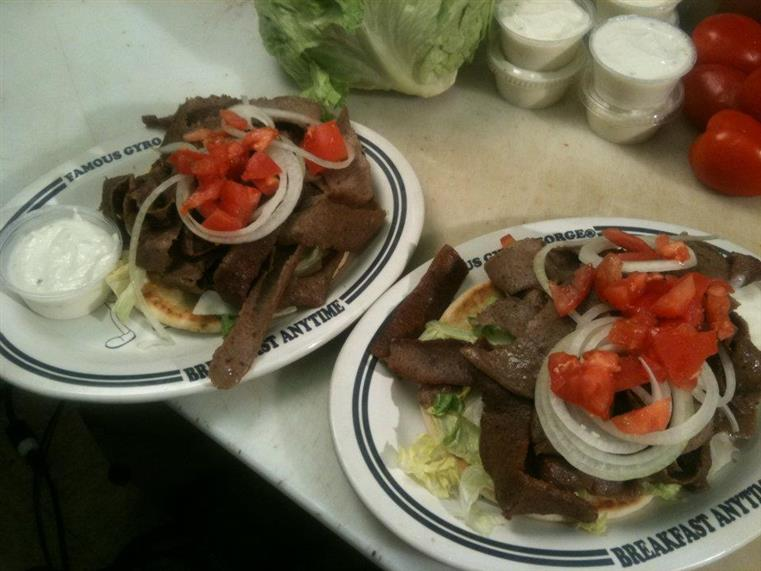 Two gyro platters with tomatoes and onions, side of tzatziki sauce on counter