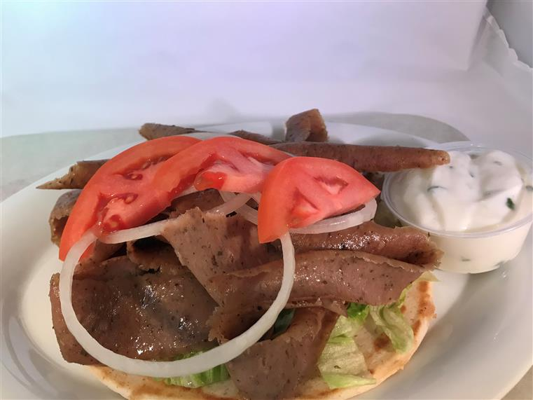 lettuce, gyro meat, onions, and tomato on a pita with a white dipping sauce on the side