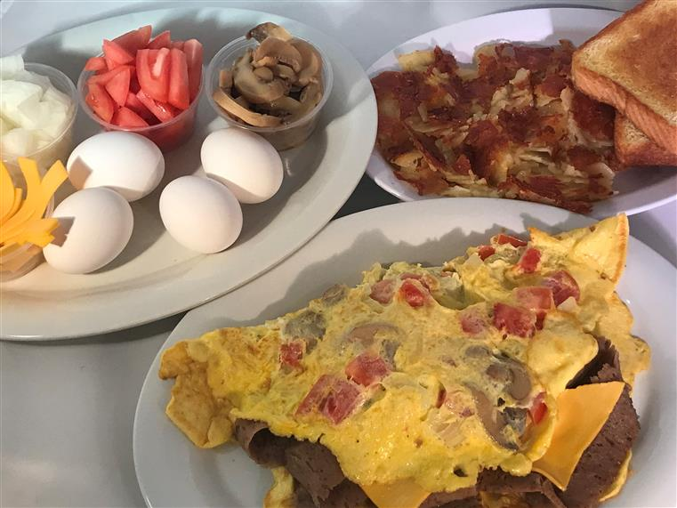 a plate eggs, mushrooms, tomato, onions, and cheese. a plate with an omlet and gyro meat. a plate with hasbrowns and toast