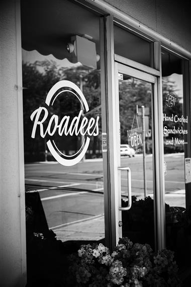 exterior view of roadees cafe window decal with open sign on door