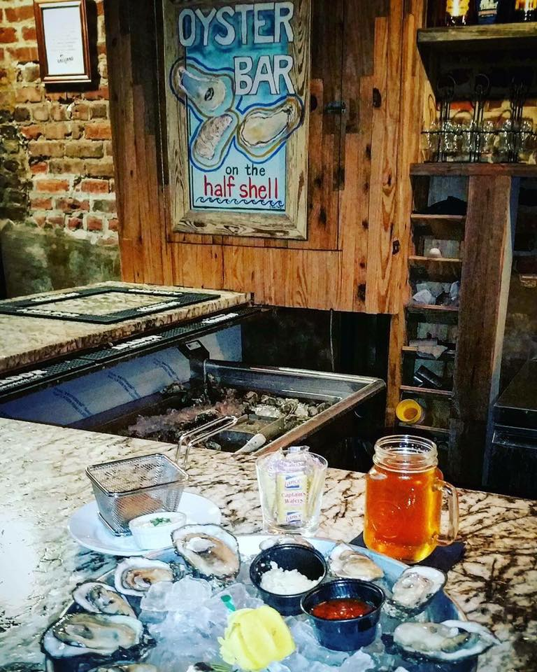 Oysters on the half shell on a counter top with a beer in a mug