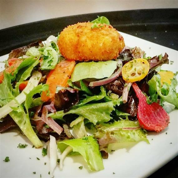 Roasted beets, local citrus, shaved fennel, red onions, & mixed baby greens tossed in a Northshore honey & black pepper vinaigrette, topped with almond crusted goat cheese