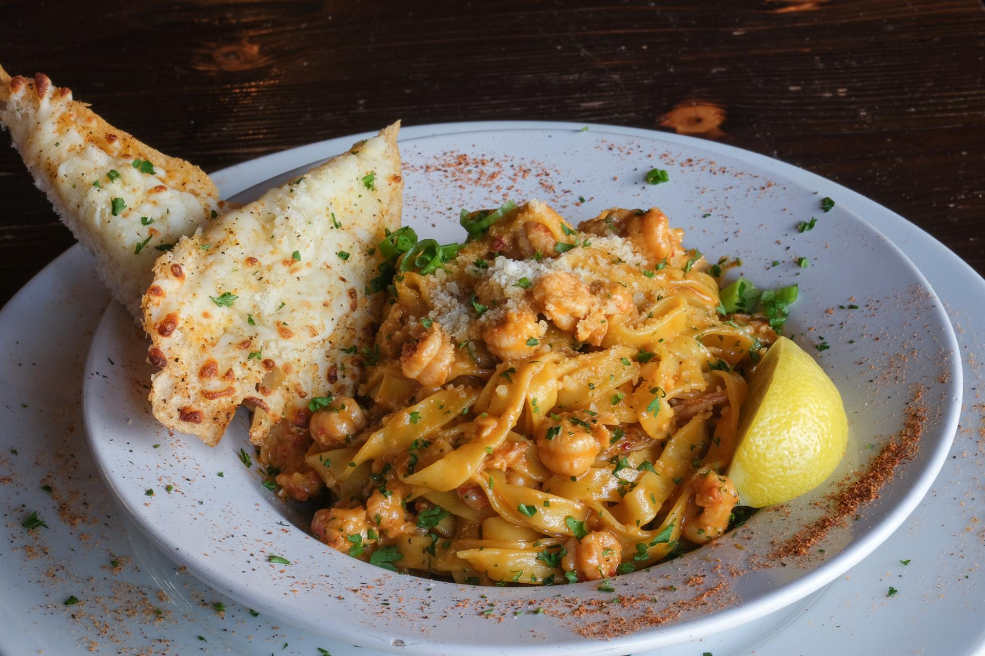 Crawfish Pasta Monica. Wild caught Louisiana crawfish tails sautéed with Creole seasonings & white wine in a light cream sauce over fresh fettuccine with toasted cheese bread