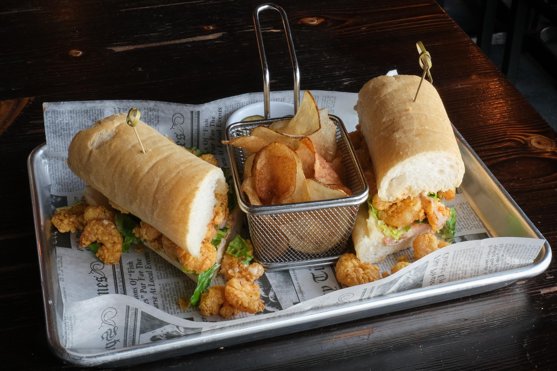 Po Boy sandwich with a basket of chips
