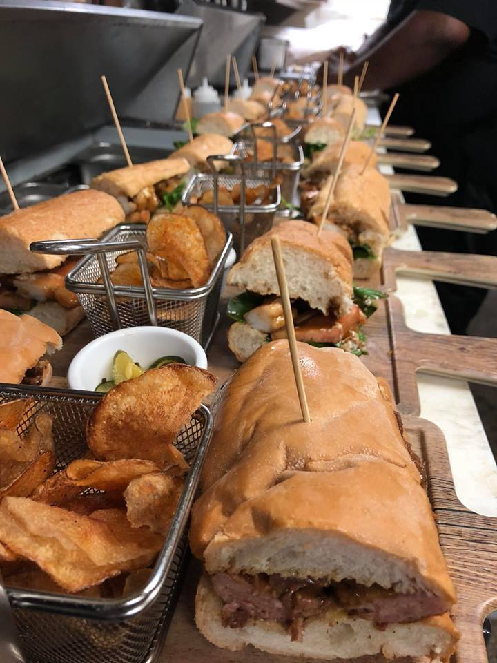 An assortment of po boys on wooden boards with a side of chips