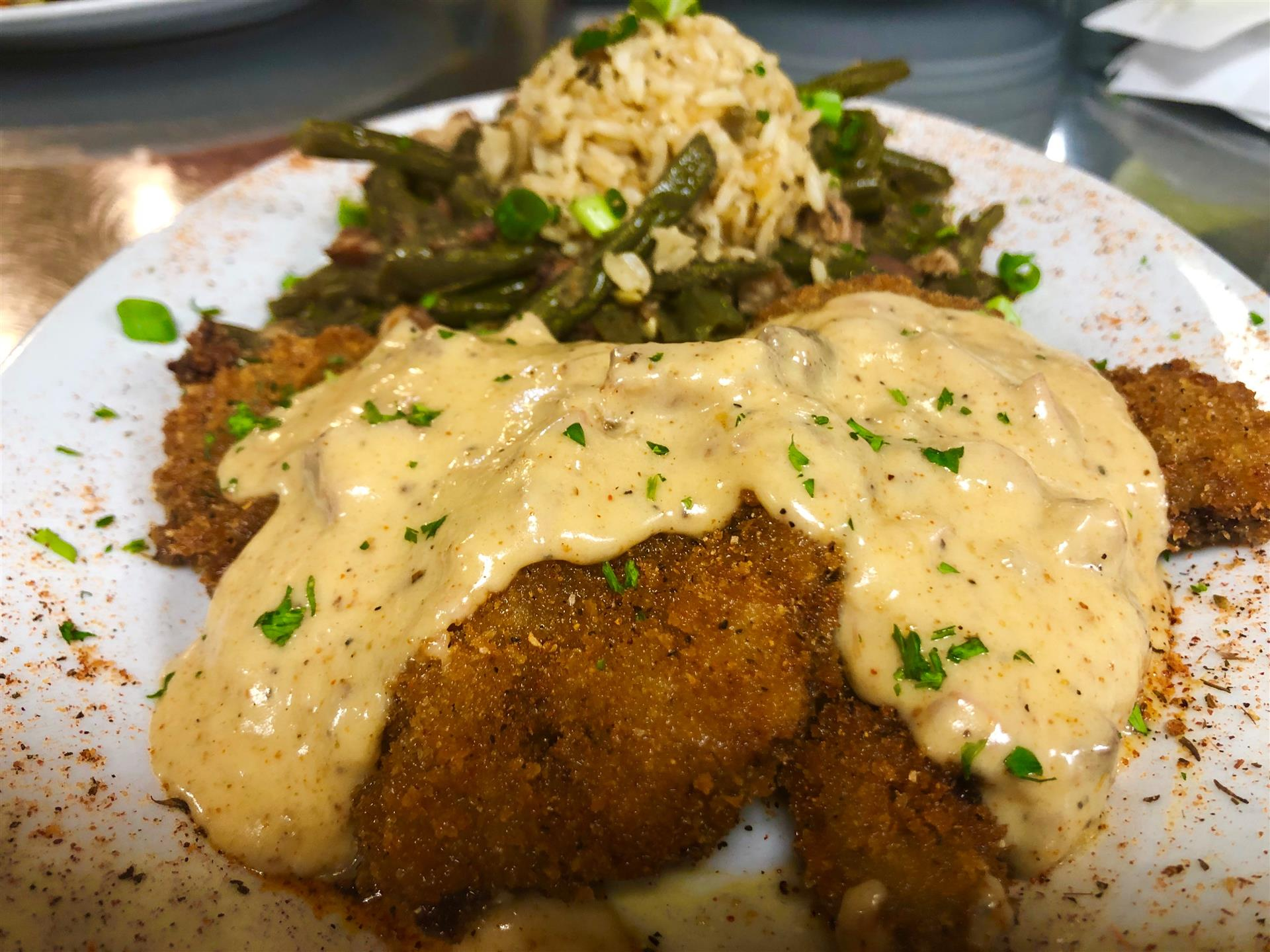 Country Fried Filet Mignon. Topped with tasso gravy, served with bacon smothered green beans with new potatoes & rice