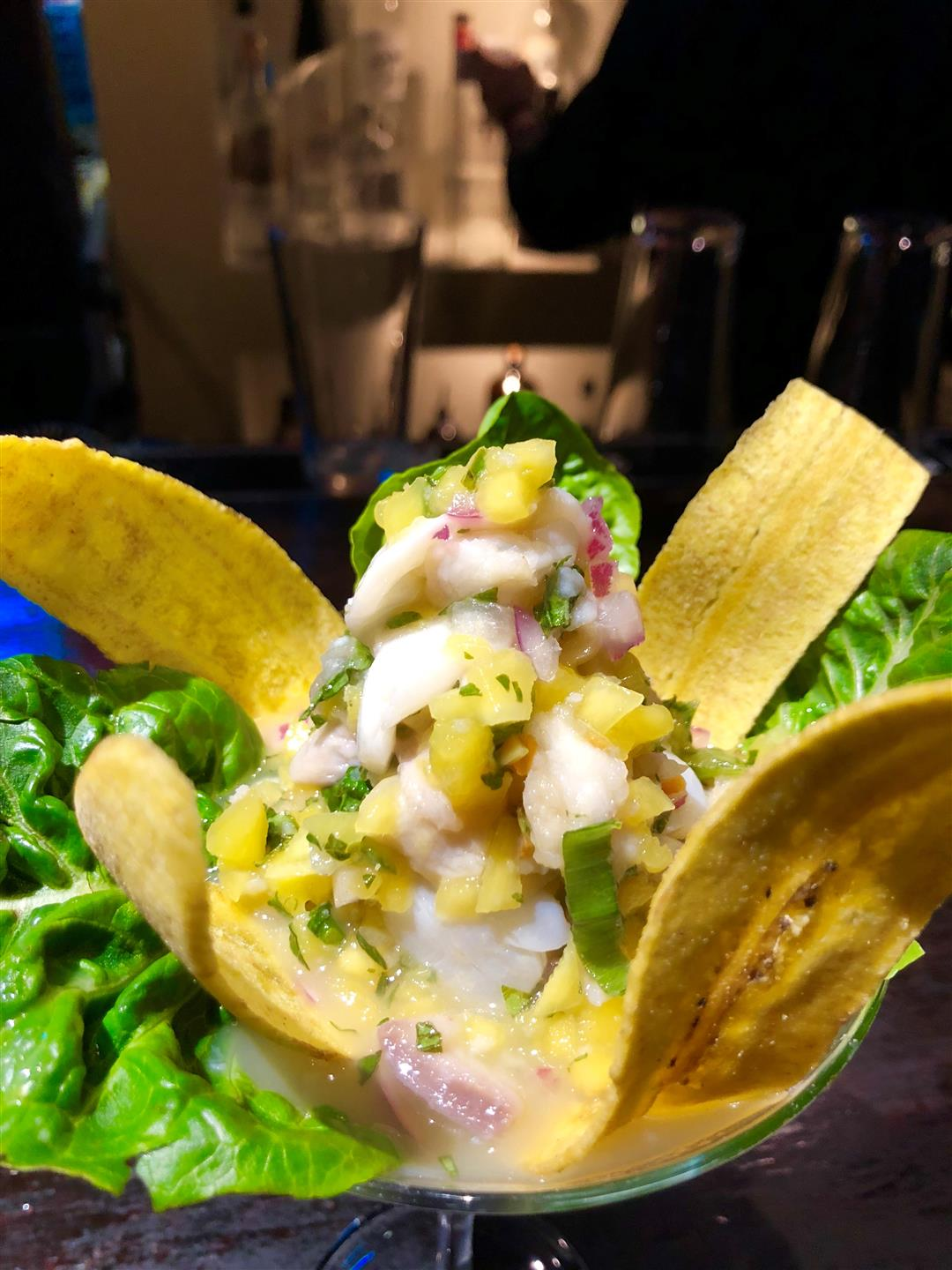 Shrimp ceviche topped with sliced avocado and plantain chips