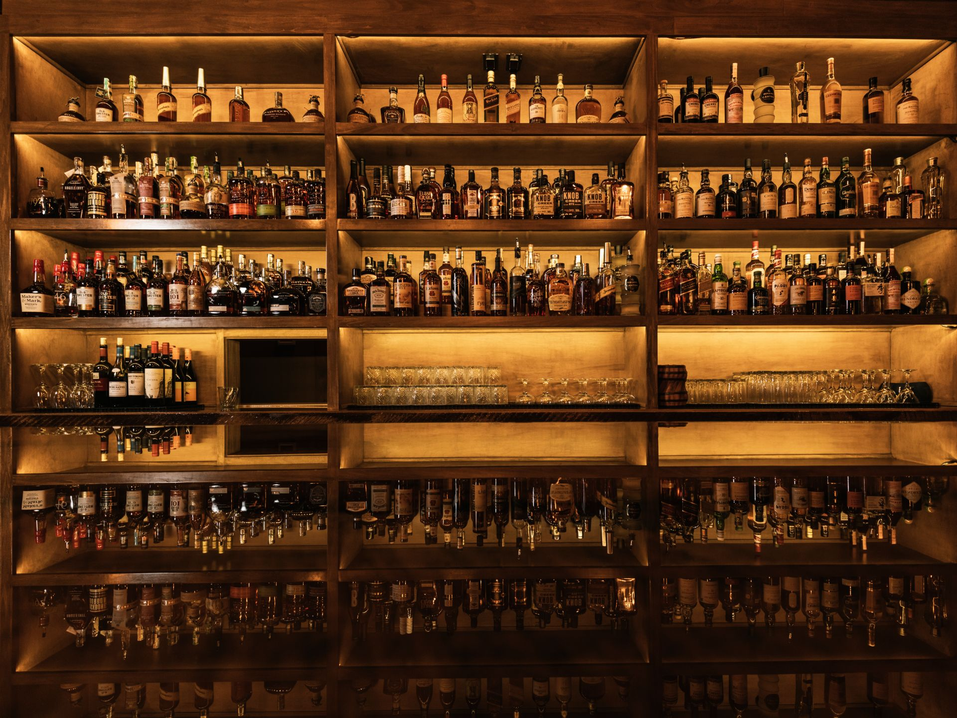 A large selection of bourbons and whiskies on a wooden shelf