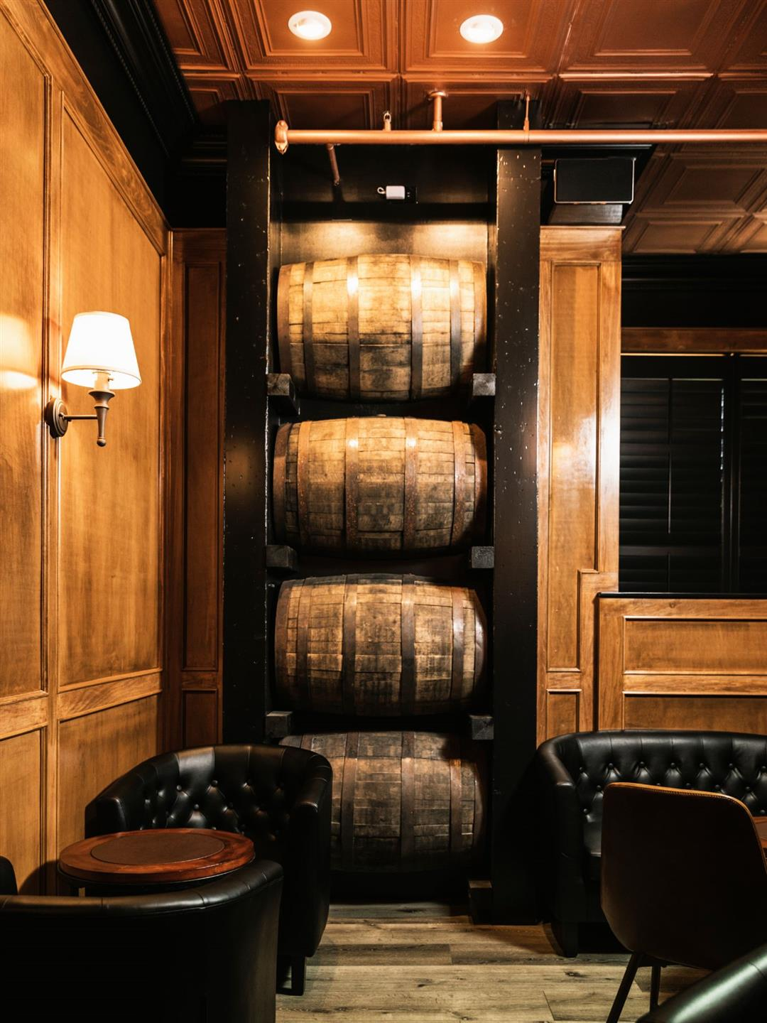 Wooden whiskey barrels stacked up in a corner beside leather chairs