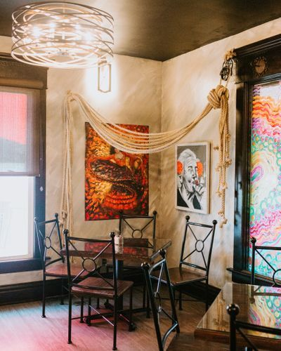corner of the dining room with table and chairs with rustic eclectic decorations and lighting with paintings on the walls