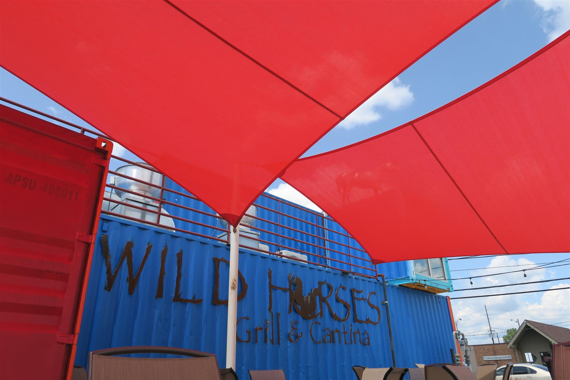 view of wild horses grill and cantina logo on side of storage container with over hang canopies above