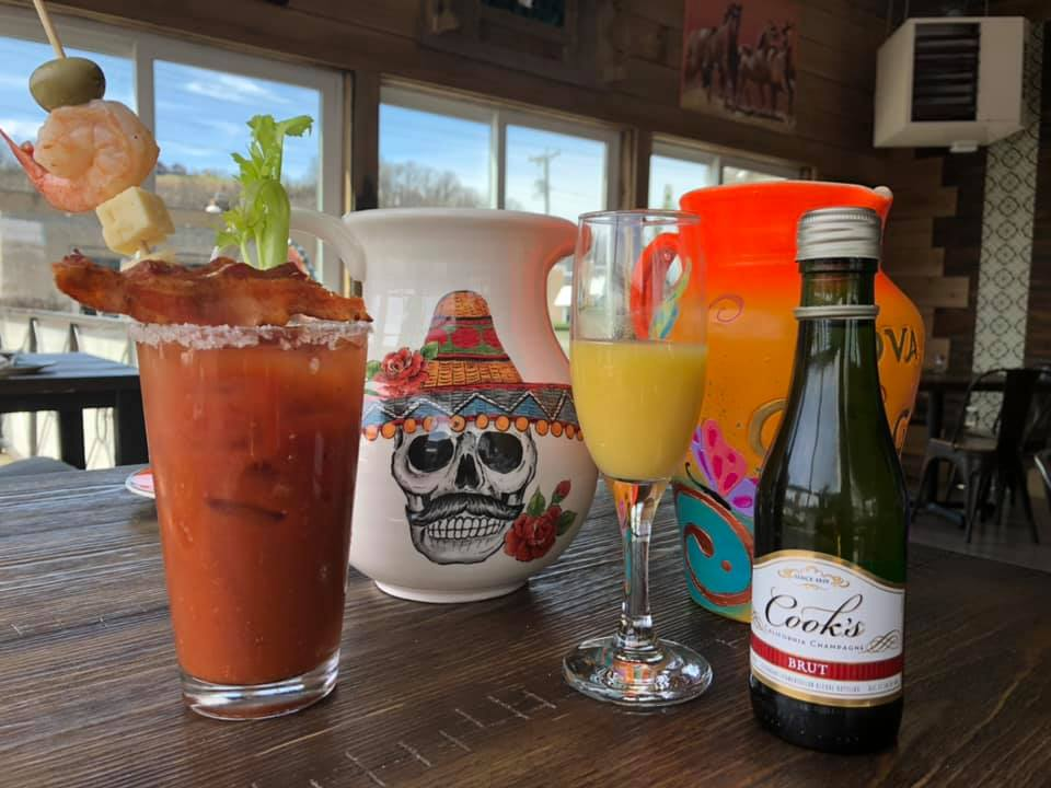 bloody mary and mimosa with a bottle of crooks outside on a table