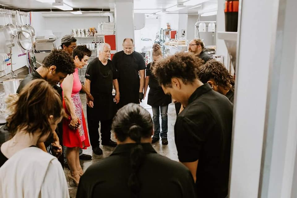 marrialana owner and staff in a prayer circle in the kitchen