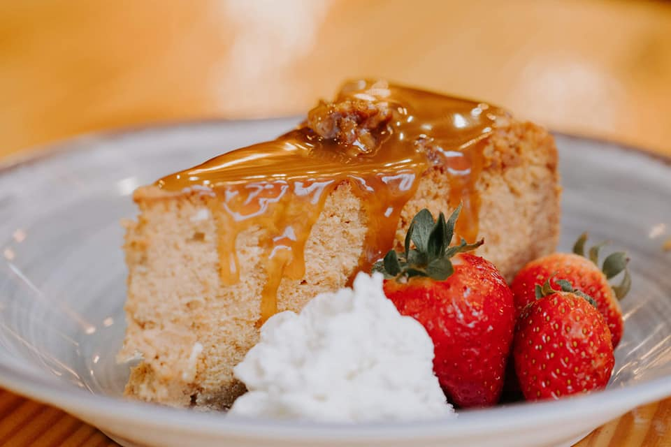 apple pecan crunch a la mode with caramel sauce on top served with strawberries