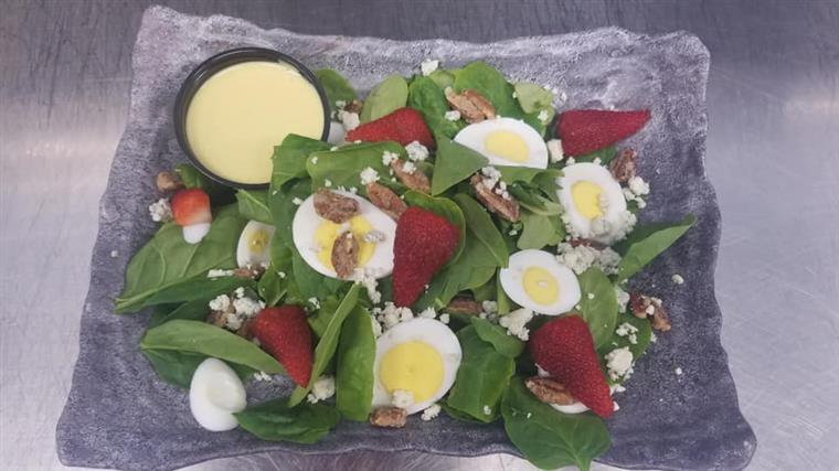 Spinach Salad. Spinach greens tossed with candied pecans, fresh strawberries, Bleu Cheese Crumbles and sliced Egg served with warm Bacon/Honey Mustard Dressing and French Bread.