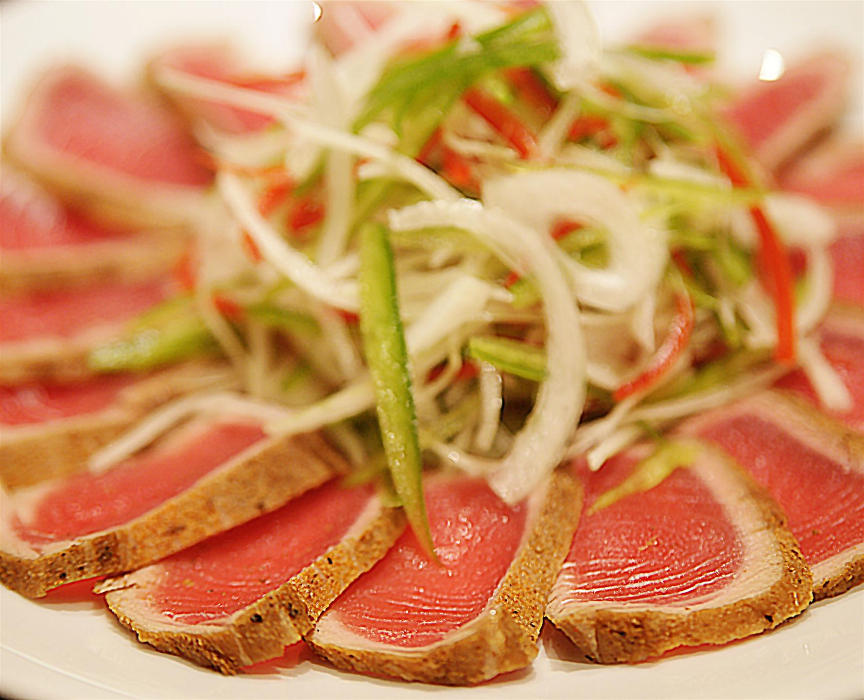 ahi tuna on a circular platter with vegetables