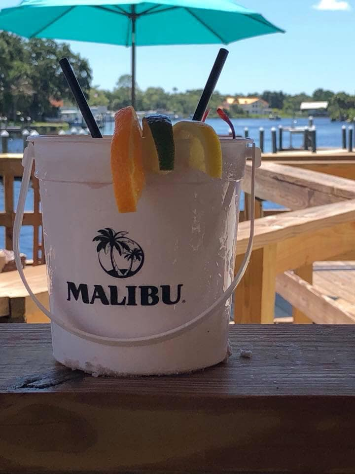 Large Malibu branded bucket with slices of orange, lime and lemon on the rim with straws