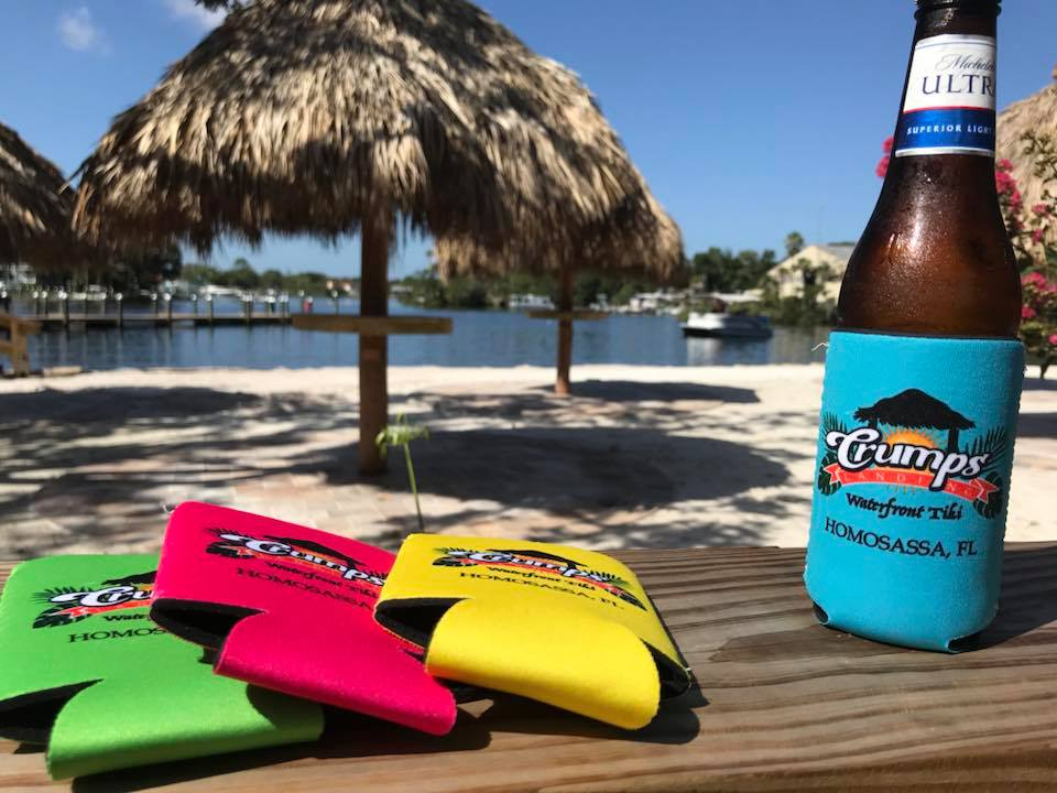 Three colored beer koozies on a wooden ledge next to a beer