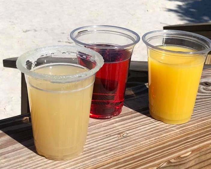 three assorted cocktails in plastic cups on the deck.