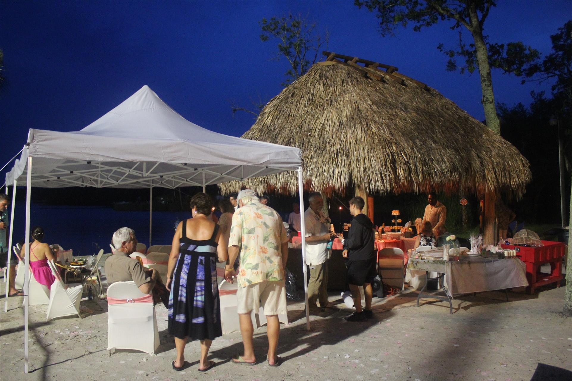 smaller tiki hut area with people enjoying food and drinks.