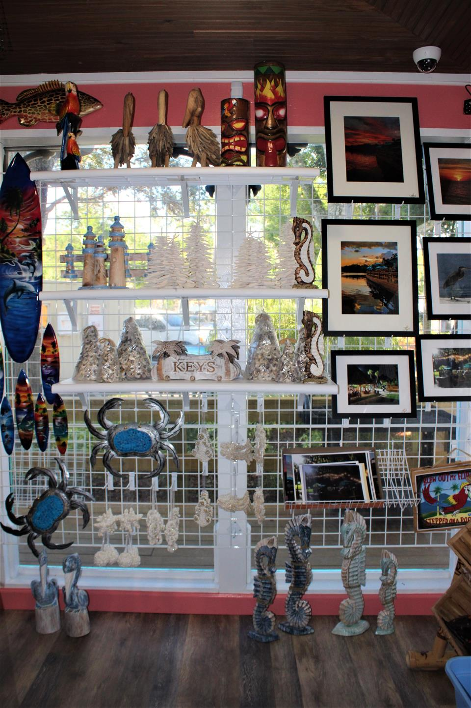 a gift shop that has pictures, tikis, surfboard, crab, seahorse, lighthouse, and palm tree wall decor