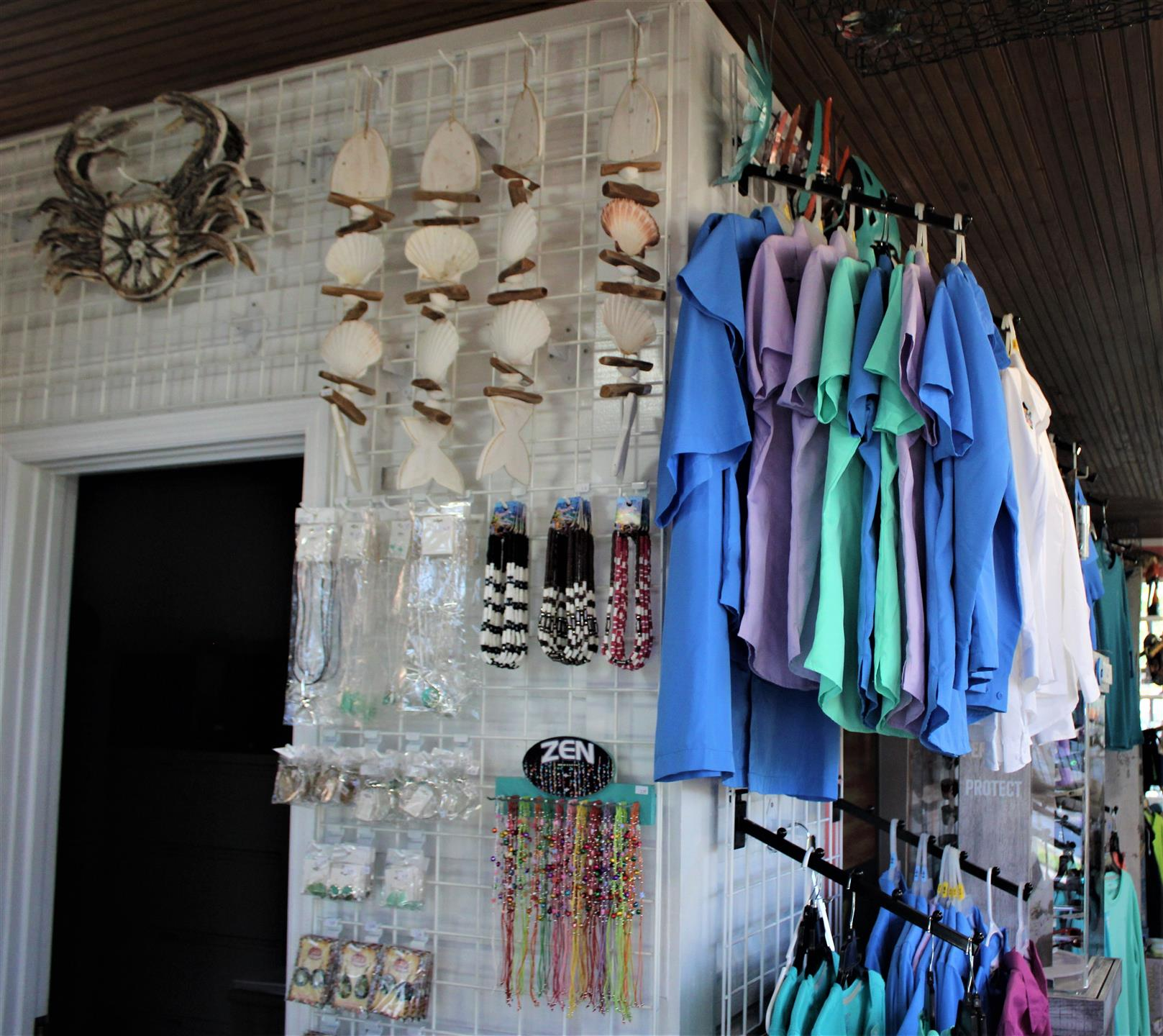 a gift shop with t-shirts, necklaces, bracelets, earrings, and seashell and crab wall decor
