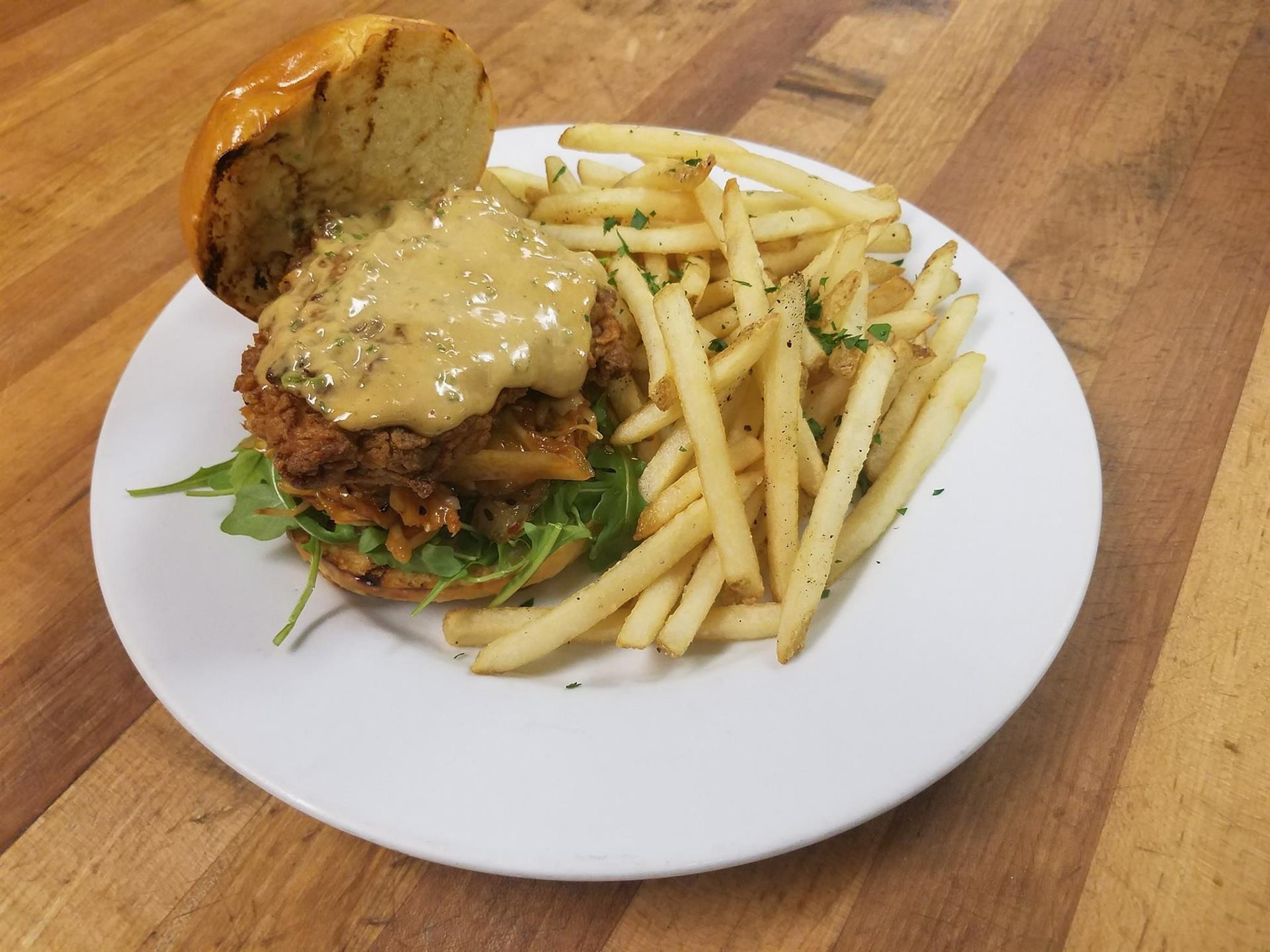 Asian Fried Chicken Sandwich With Arugula, House Kimchi, Sweet Ginger Soy Aioli, on a Toasted Brioche Bun, served with French Fries