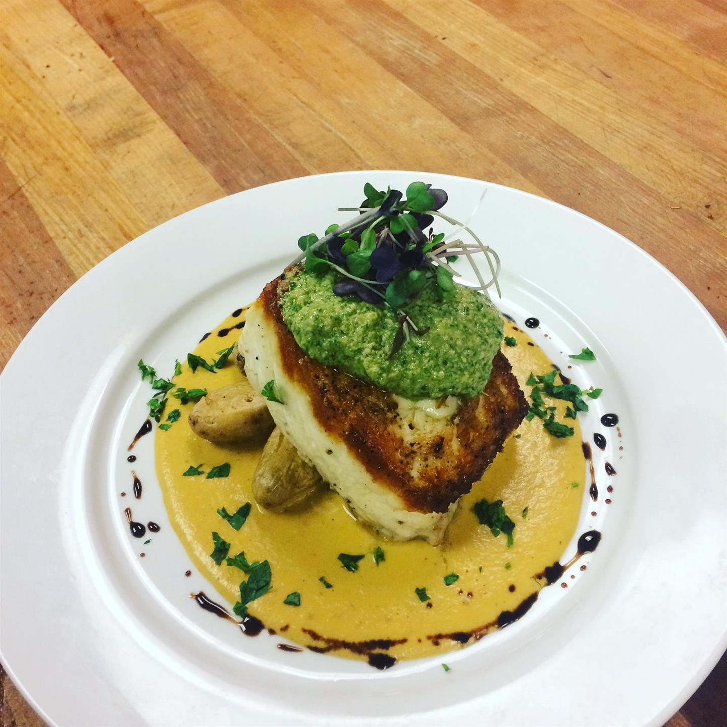 Seared Pork Chop topped with pesto and garnish on a plate with sauce