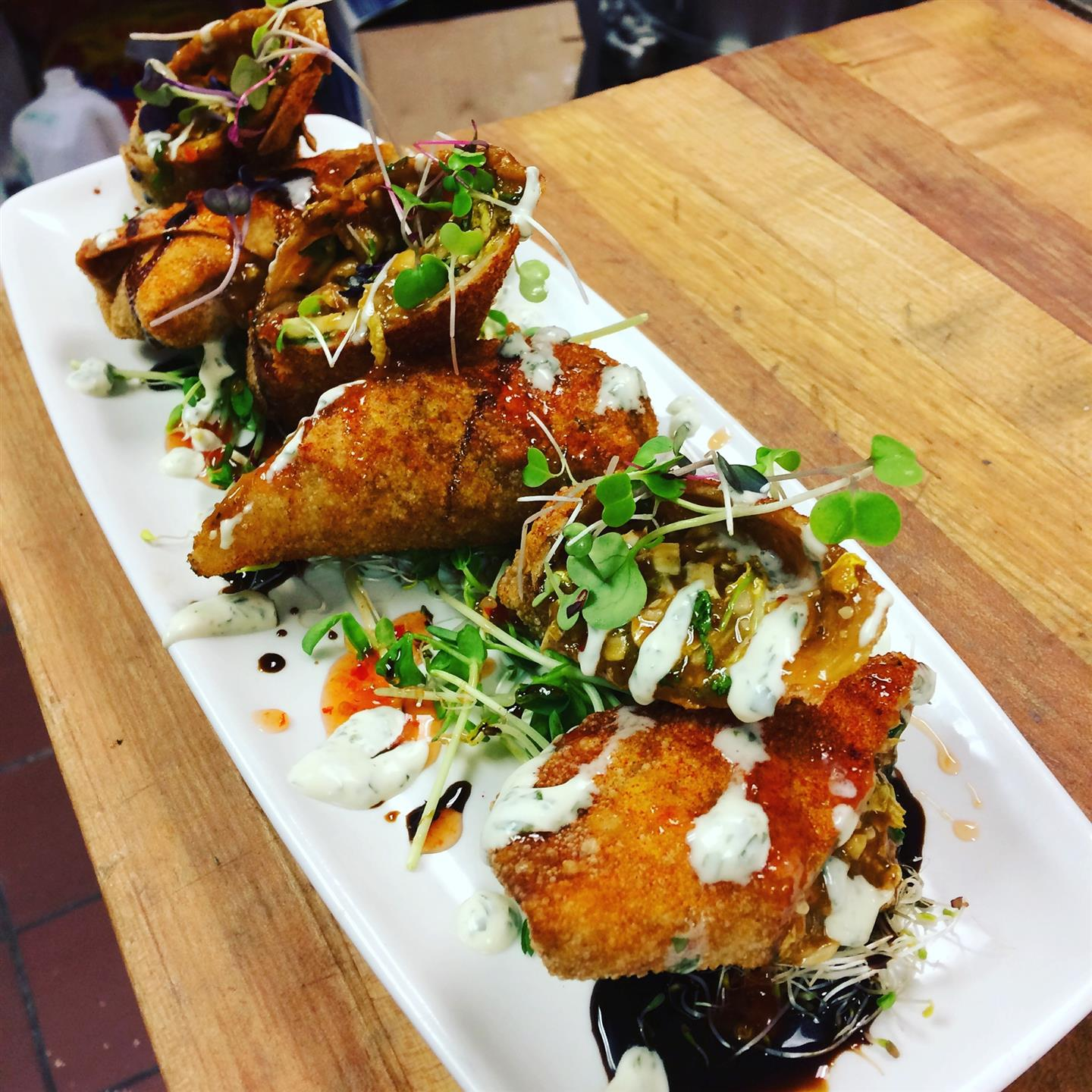 Egg rolls topped with garnish and sauce drizzled on top of a plate