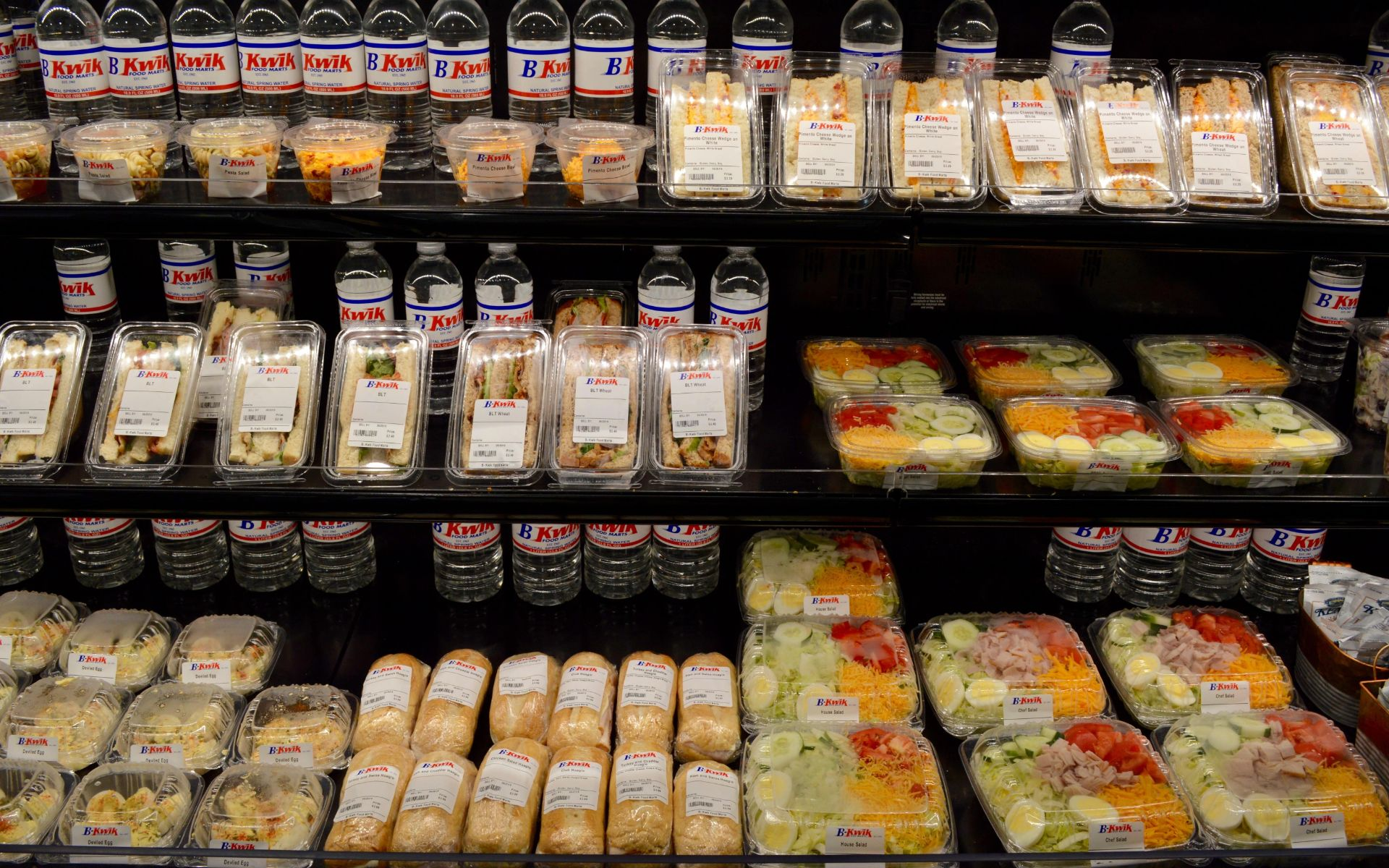 An assortment of pre-packaged sandwiches, salads and bottles of water on a shelf