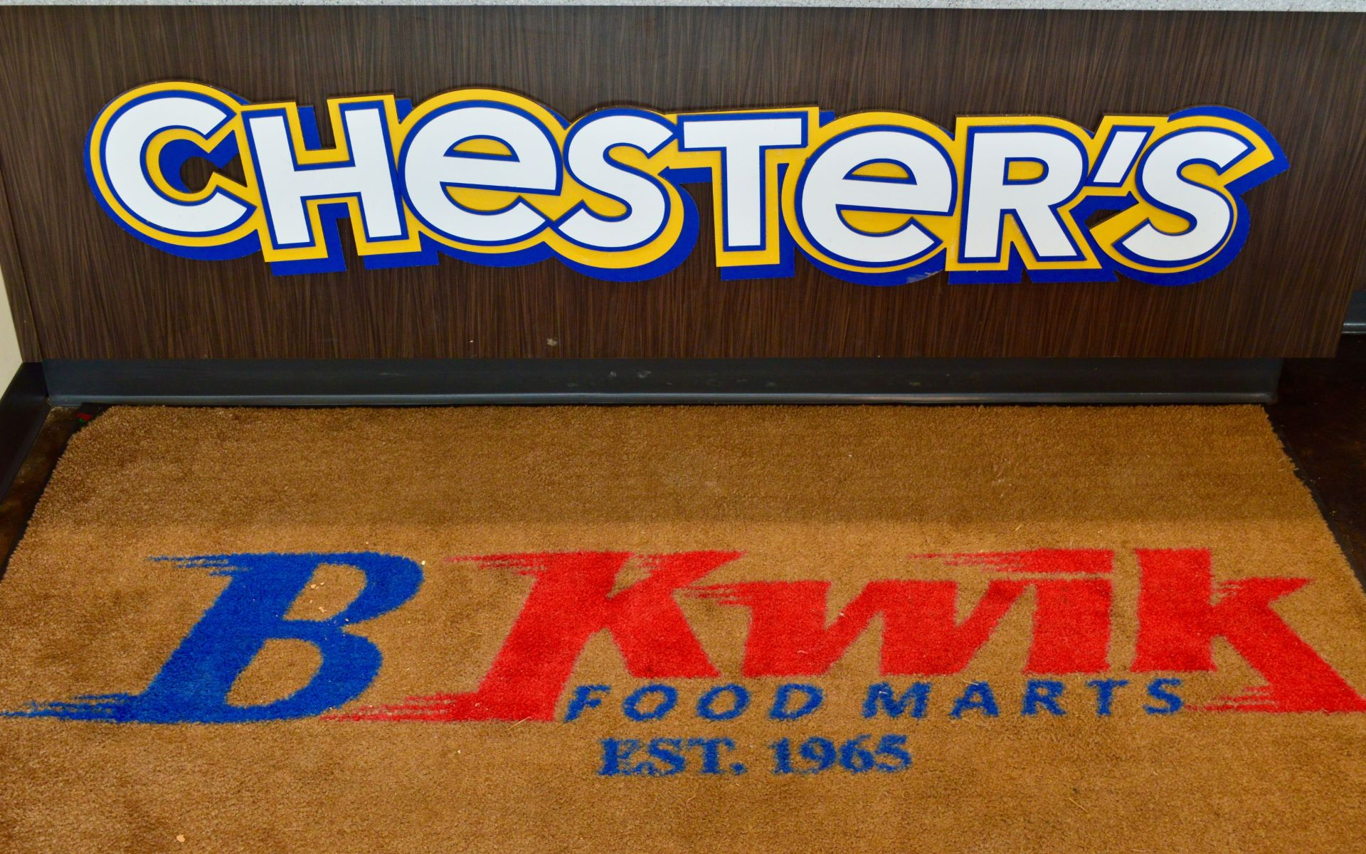 Chester's sign on the side of a counter with a B Kwik Food Marts branded carpet on the floor