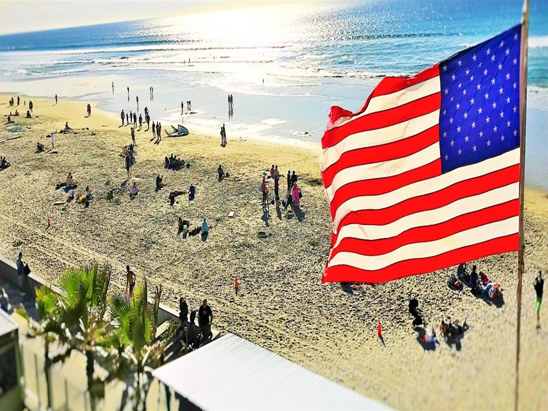 american flag waving infront of beach full of people