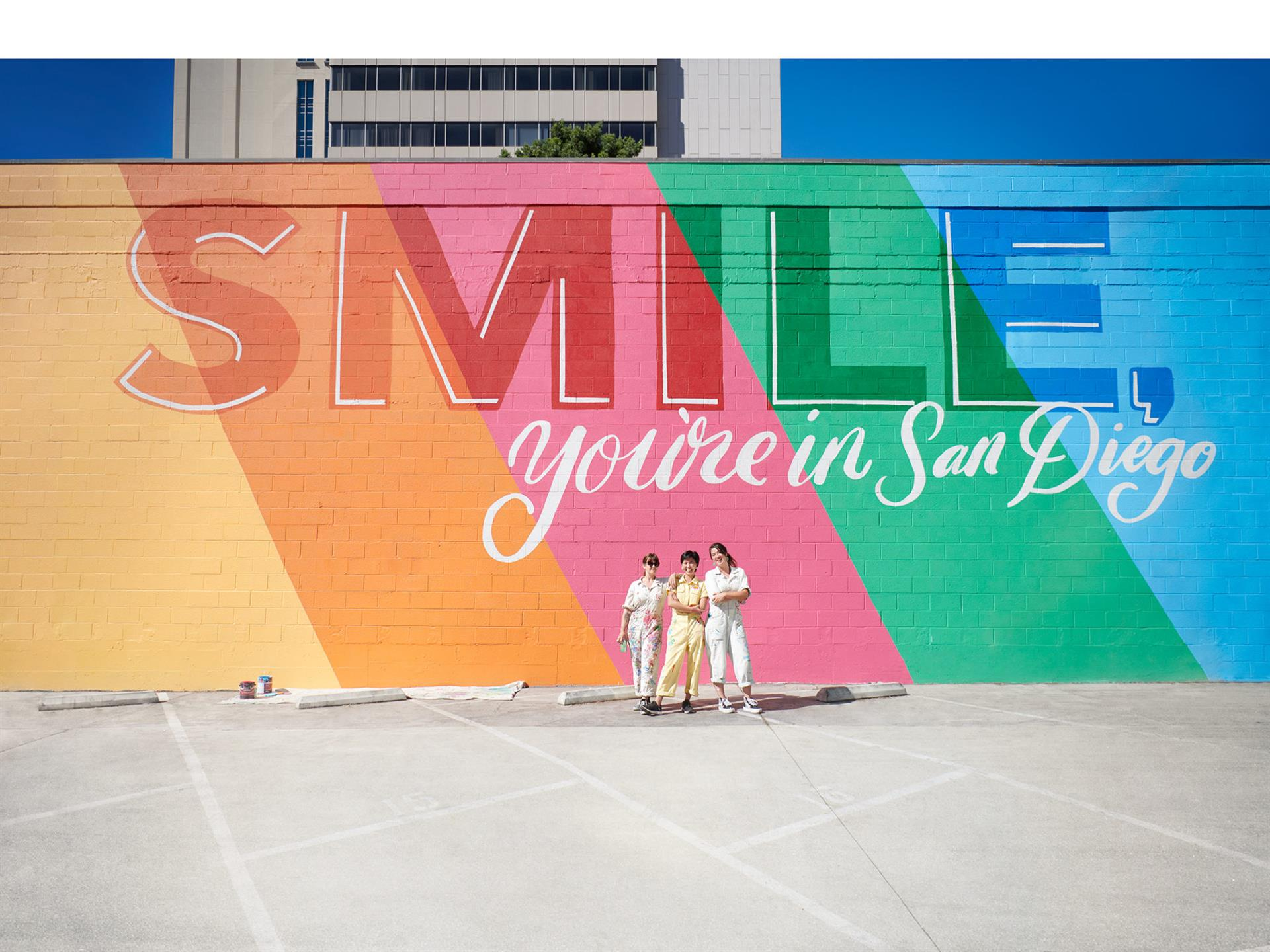 """Smile youre in San Diego"" rainbow mural behind three people posing for a picture"