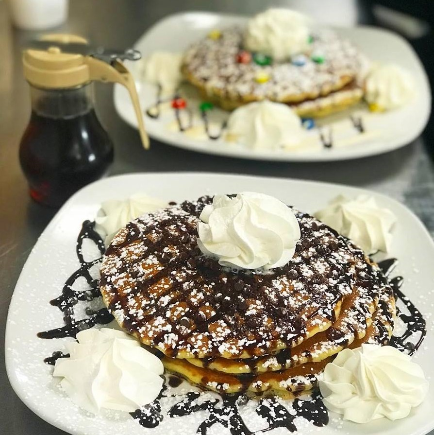 Chocolate chip and Birthday pancakes with whipped cream and powdered sugar