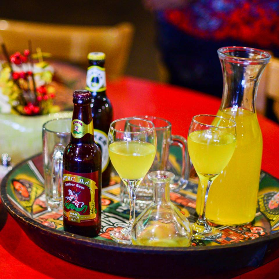 Ethiopian beer in a bottle next to glasses filled with homemade honey wine