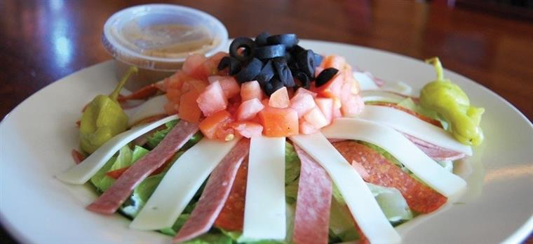 Antipasto dish with assortment of meats and cheese on a dish topped with tomatoes and olives