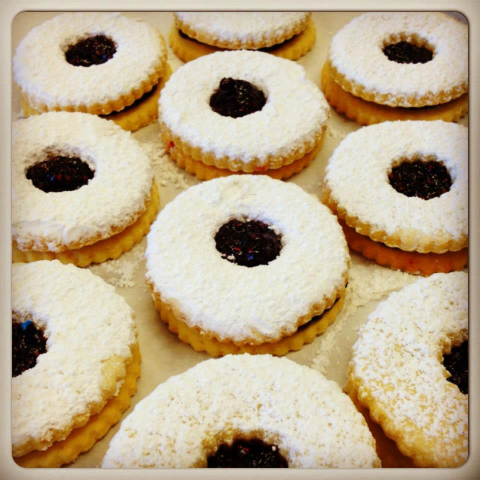 sheet tray of italian linzer cookies with jam in the middle