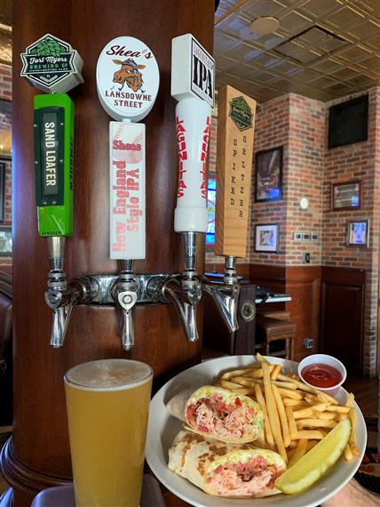 Wrap with turkey, bacon, lettuce and tomato with french fries and a pickle on the side. Ketchup for dipping and a cold beer for drink all lined up on the bar near the taps.