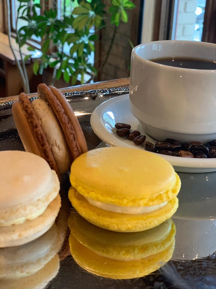 assortment of macaroons with coffee cup with coffee beans on a dish