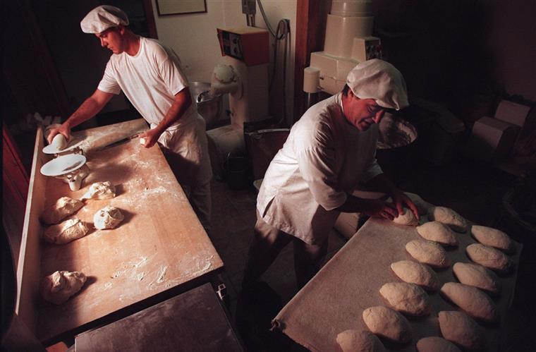 two men kneading with dough in a bakery