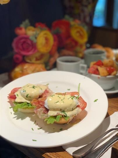 Eggs Benedict on an english muffin with salmon, arugula, and hollandaise sauce
