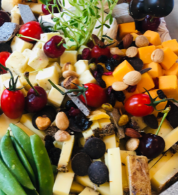 assortment of grapes and cheese, and snap peas on a tray