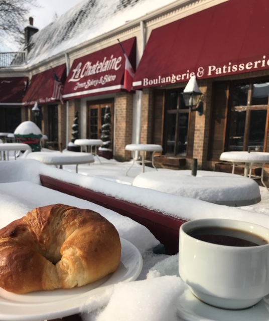 cup of coffee and croissant on a table covered in snow