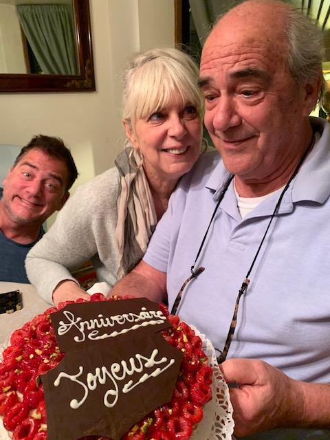 Family posing for picture while man is holding a cake