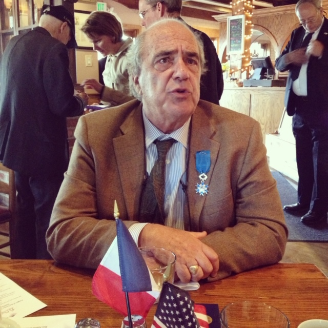 man sitting at a a table wearing a suit with a medal