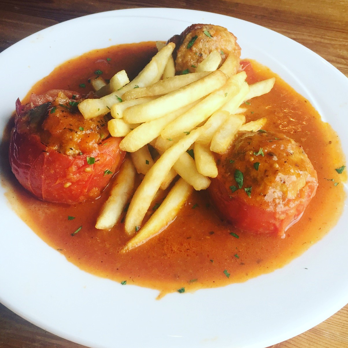 3 meatballs topped with fries in sauce on a dish
